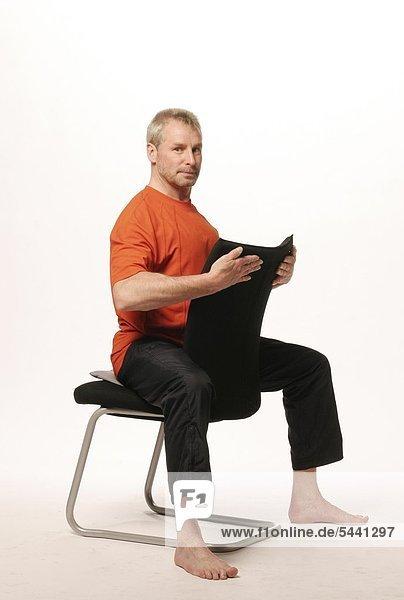 lterer mann sitzt auf einem stuhl im reitersitz mit dem gesicht zur lehne beide h nde. Black Bedroom Furniture Sets. Home Design Ideas