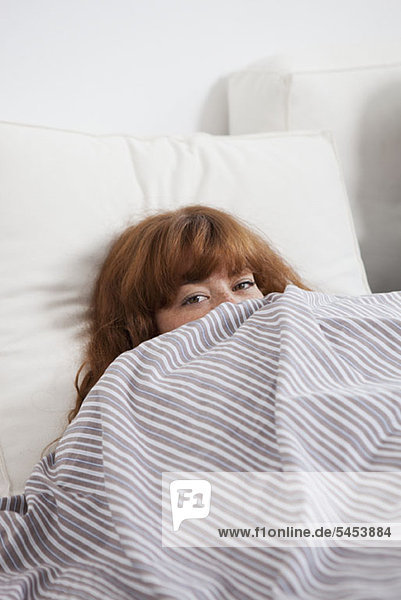 Eine Frau wird hinter einer Bettdecke im Bett