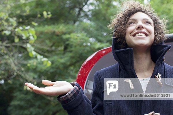 Lächelnde Frau steht im Regen