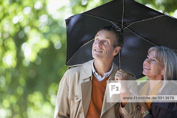 Paar unter einem Regenschirm schaut nach oben