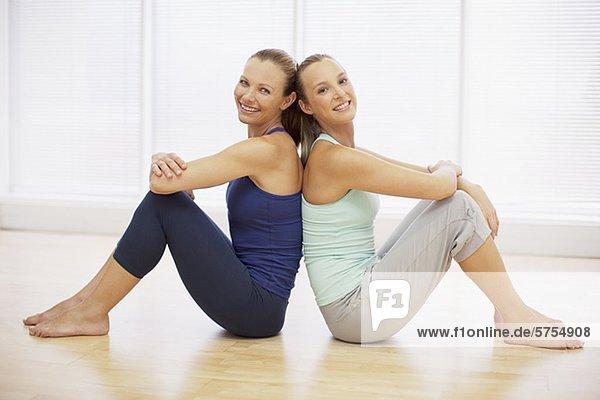 zwei l chelnde frauen sitzen r cken an r cken im fitnessstudio portrait lizenzfreies bild. Black Bedroom Furniture Sets. Home Design Ideas