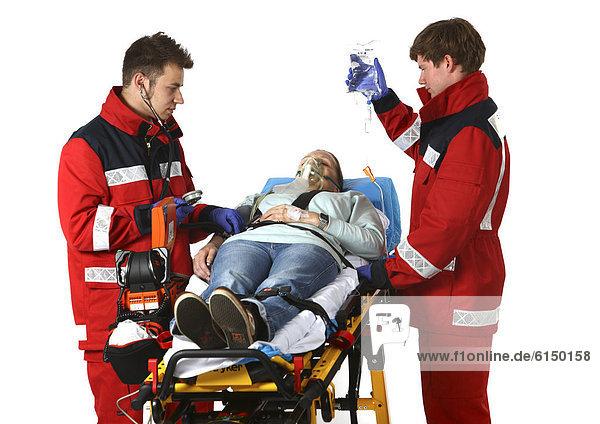 Rettungssanitäter kleidung  auf fahrbarer Krankentrage, bekommt eine Infusion, Berufsfeuerwehr ...