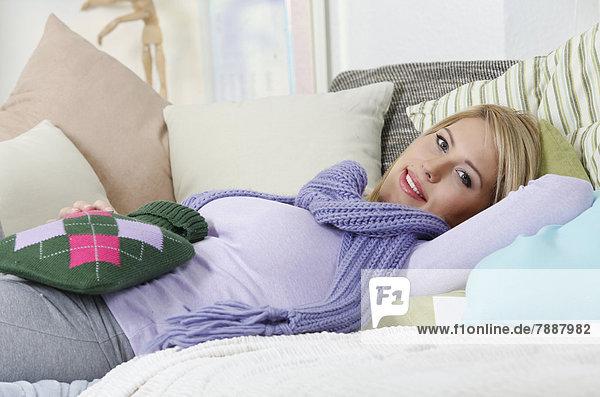 junge frau liegt mit w rmflasche auf dem sofa lizenzpflichtiges bild bildagentur f1online. Black Bedroom Furniture Sets. Home Design Ideas