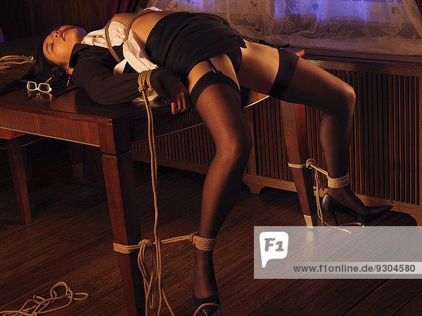 Halbnackte Frau, mit Seilen an einen Tisch gefesselt