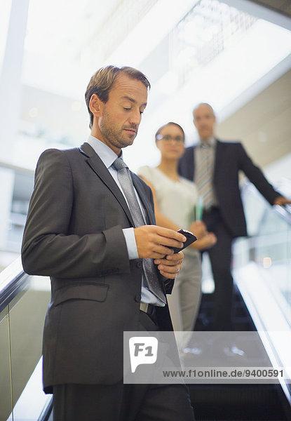 Rolltreppe,Handy,benutzen,Geschäftsmann