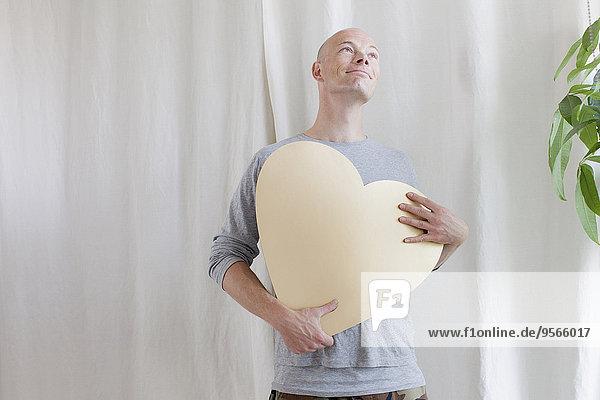 Interior,zu Hause,Form,Formen,Mann,halten,reifer Erwachsene,reife Erwachsene,herzförmig,Herz