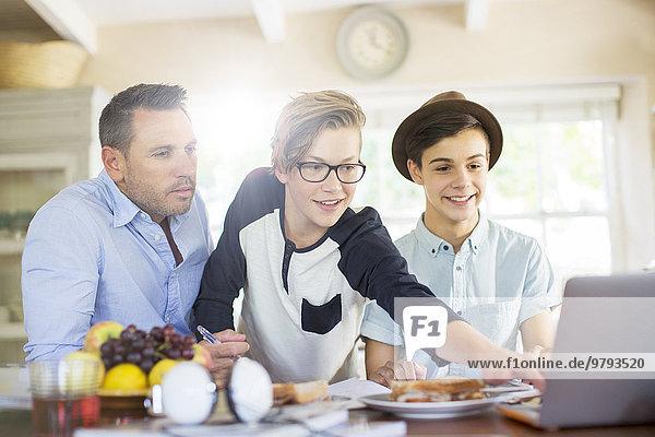 benutzen,Jugendlicher,Notebook,Junge - Person,Menschlicher Vater,am Tisch essen,Zimmer