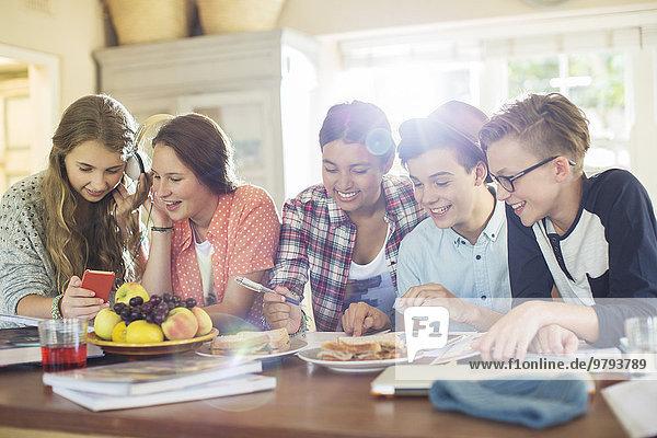 benutzen,Jugendlicher,am Tisch essen,Zimmer,Gerät,Elektronik,Tisch