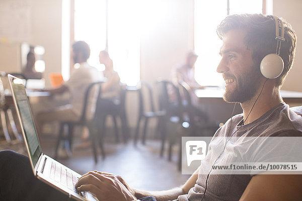 Notebook,Geschäftsmann,Freizeitbekleidung,arbeiten,Kopfhörer,Büro,Kleidung