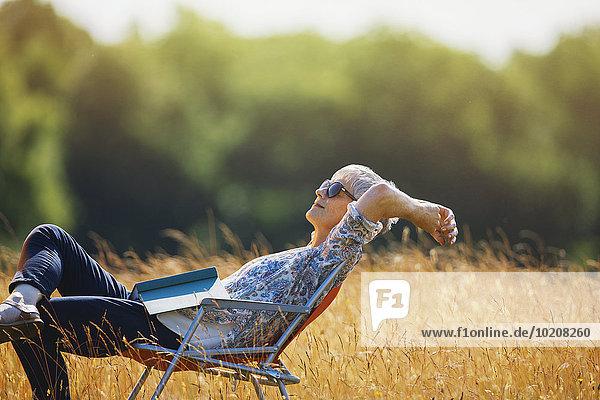 Senior,Senioren,Frau,Entspannung,Buch,Feld,Sonnenlicht,Taschenbuch,Sorglosigkeit