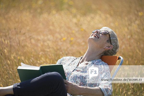Senior,Senioren,Frau,lachen,Buch,Feld,Sonnenlicht,Taschenbuch,vorlesen
