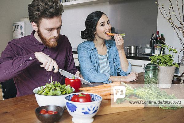 nebeneinander,neben,Seite an Seite,Frau,Mann,Küche,Möhre,rot,jung,Peperoni,hacken,essen,essend,isst,Tisch,Glocke