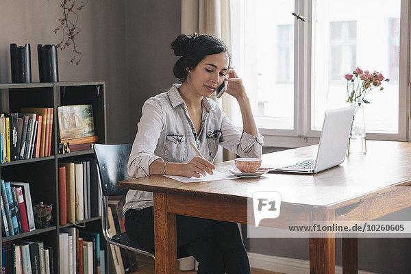 Handy,Interior,zu Hause,junge Frau,junge Frauen,benutzen,Notebook,Kurznachricht,Tisch