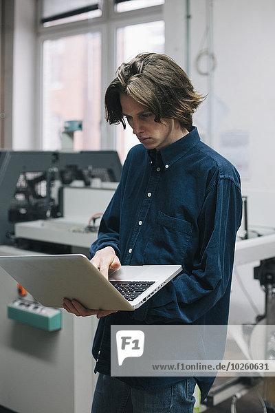 benutzen,Notebook,Technischer Beruf,jung,Fabrikgebäude