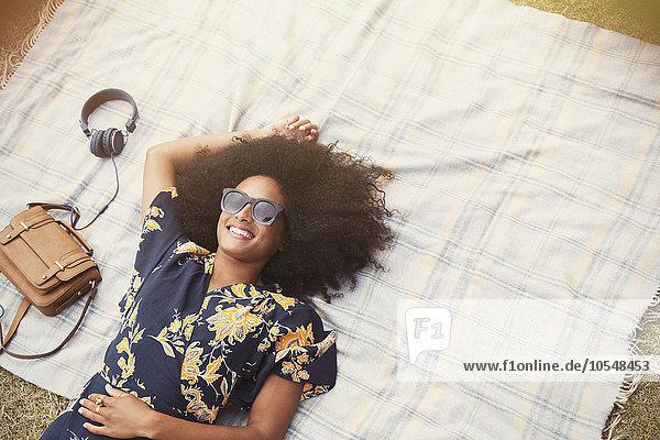 Außenaufnahme,liegend,liegen,liegt,liegendes,liegender,liegende,daliegen,krauses Haar,Afrolook,Afro,Afros,Frau,lächeln,Decke,über,Ansicht,freie Natur