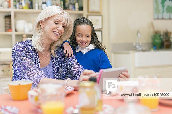 benutzen,Enkeltochter,Großmutter,Tablet PC,Tisch,Frühstück