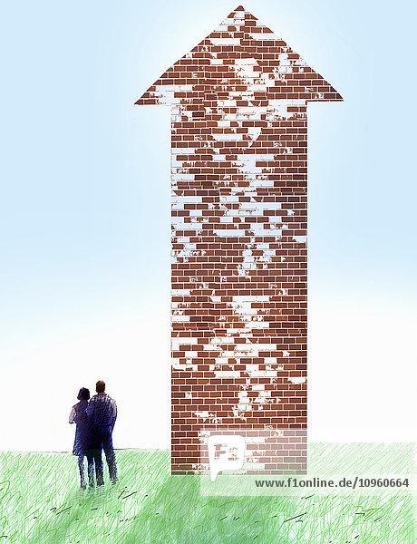 Paar schaut auf eine Pfeil in Form einer Ziegelmauer