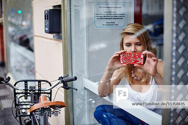 Junge Frau mit Handy hinter einer Fensterscheibe