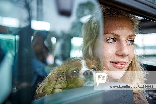 Lächelnde junge Frau mit Hund im Auto schaut aus dem Fenster