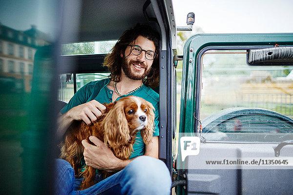 Mann mit Hund sitzt in Geländewagen