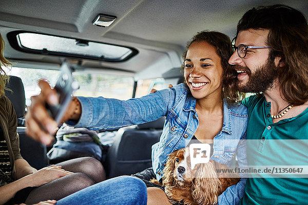 Fröhliches Paar mit Hund macht ein Selfie im Auto