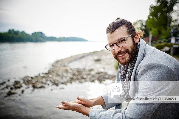 Lächelnder junger Mann mit Vollbart am Flussufer