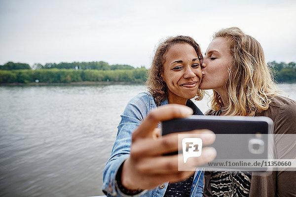 Zwei junge Frauen machen ein Selfie am Flussufer