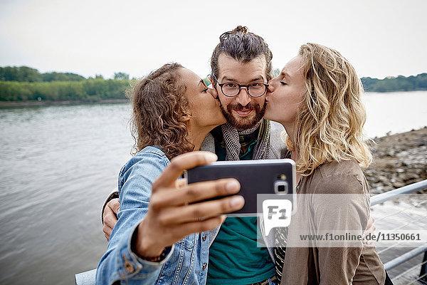 Freunde machen ein Selfie am Flussufer