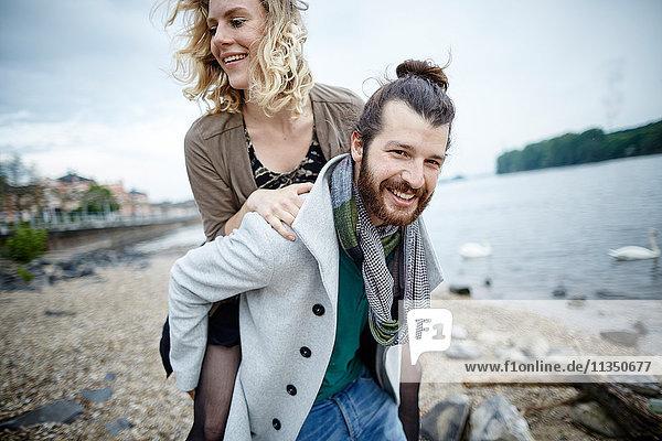 Fröhliches junges Paar am Flussufer