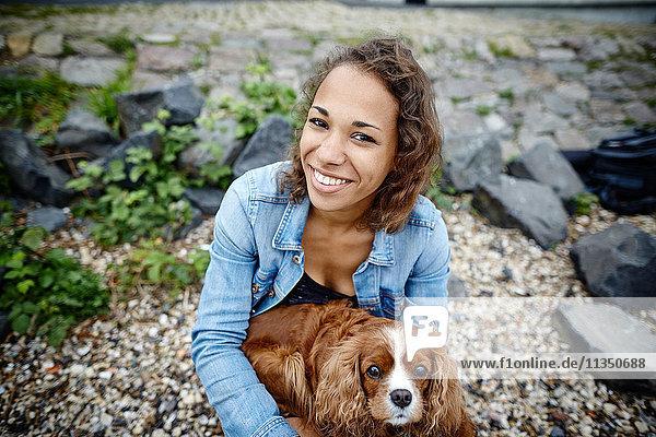 Lächelnde junge Frau mit Hund im Freien