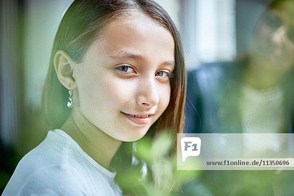 Portrait eines lächelnden Mädchens mit Mutter im Hintergrund