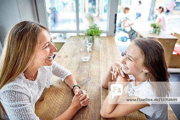 Glückliche Mutter und Tochter sitzen im Restaurant gegenüber