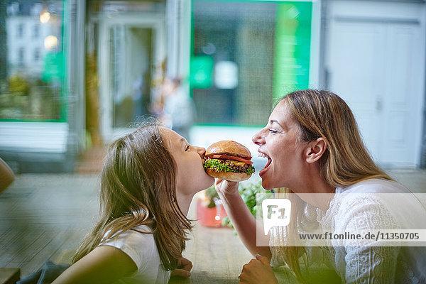 Mutter und Tochter im Restaurant teilen sich einen Hamburger