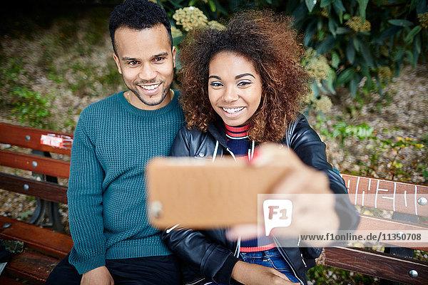 Lächelndes junges Paar auf einer Parkbank macht ein Selfie