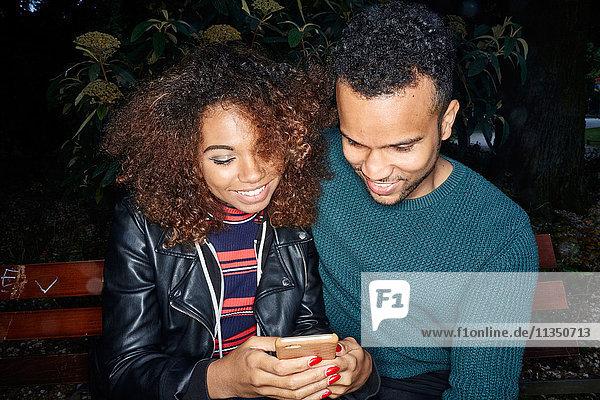 Lächelndes junges Paar auf einer Parkbank schaut aufs Handy