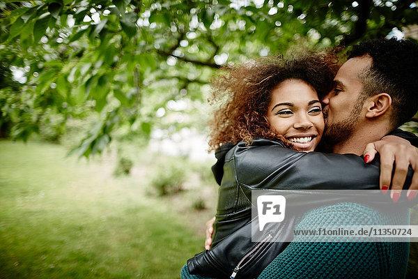 Glückliches junges Paar umarmt sich im Freien