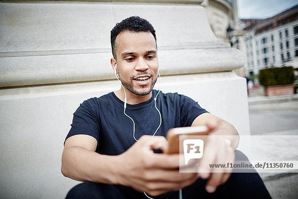 Junger Mann mit Ohrhörern und Handy im Freien
