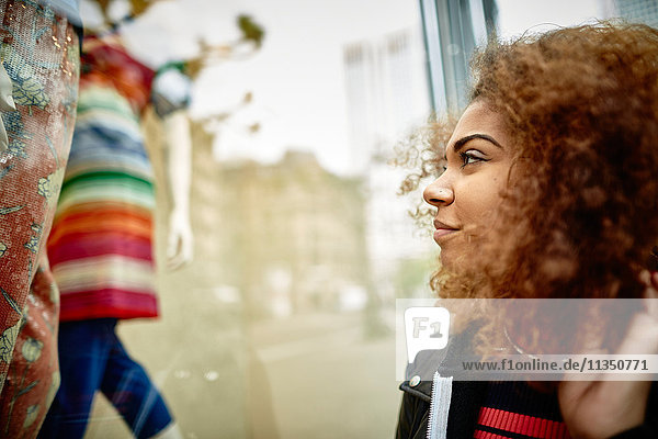 Junge Frau schaut in ein Schaufenster