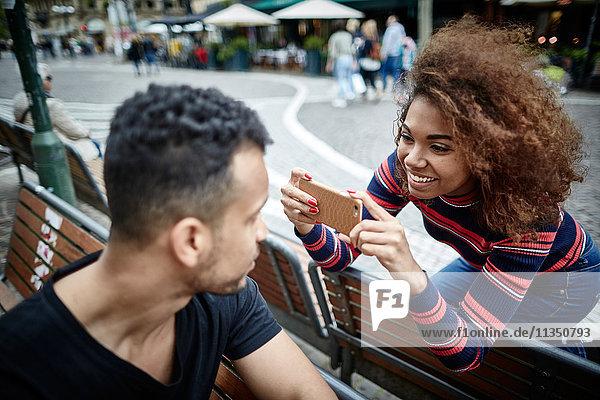 Junge Frau macht ein Handyfoto ihres Freundes