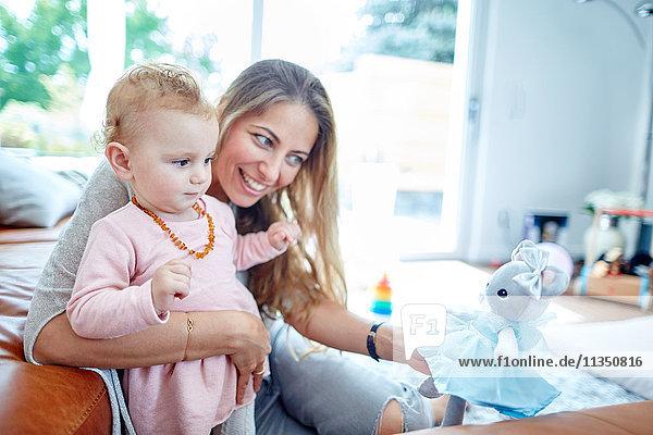 Mutter und Baby spielen mit einer Puppe