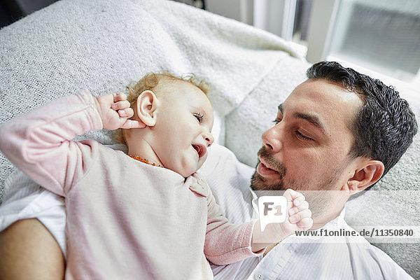 Vater und Baby liegen Zuhause