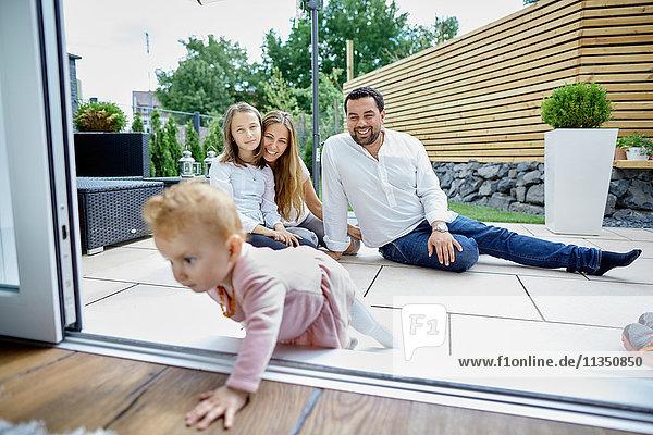 Familie auf der Terrasse schaut zu krabbelndem Baby