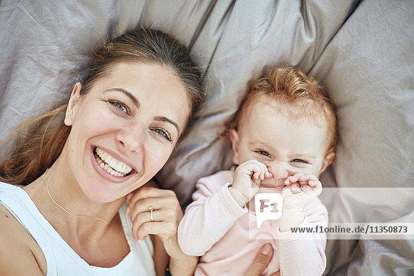 Portrait einer glücklichen Mutter und Baby im Bett