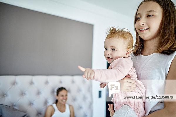 Mädchen trägt ein Baby mit Mutter im Hintergrund