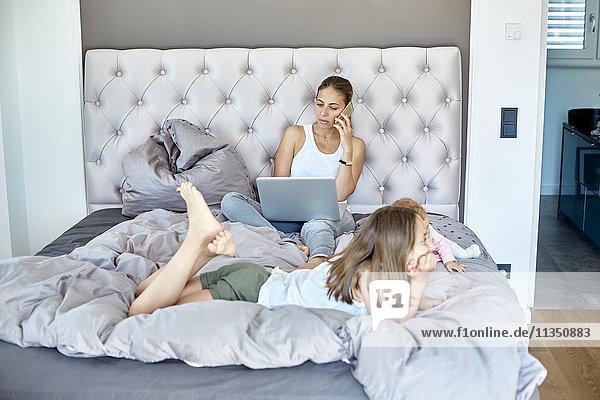 Mutter mit Laptop und Tochter und Baby im Bett