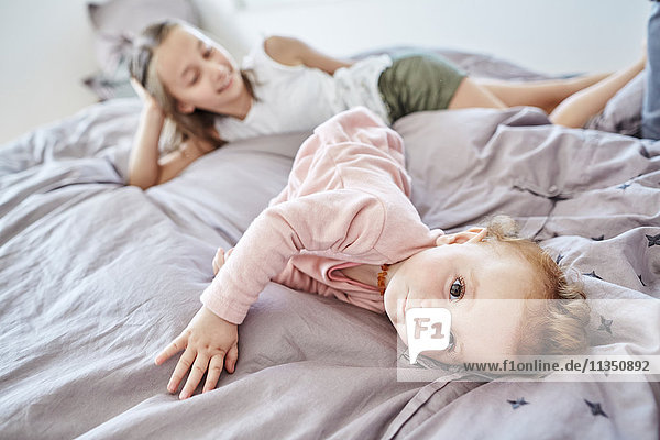 Baby liegt mit ihrer Schwester im Bett
