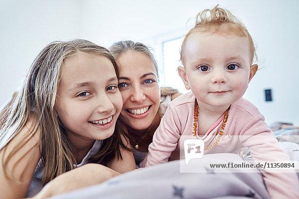 Portrait einer Mutter mit Tochter und Baby im Bett