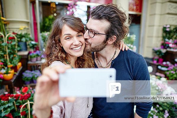 Lächelndes junges Paar macht ein Selfie vor einem Blumengeschäft
