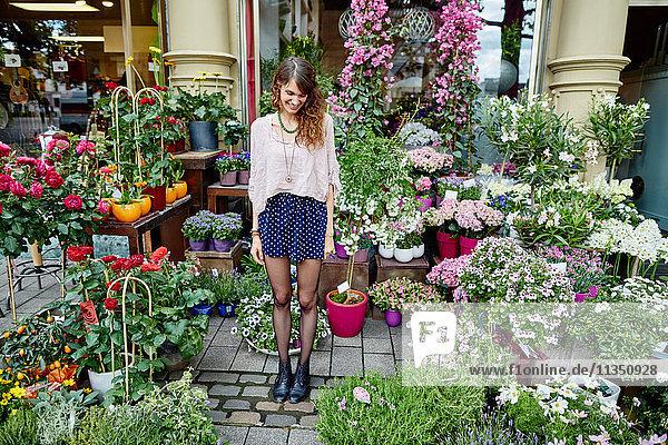 Lächelnde junge Frau steht an einem Blumengeschäft