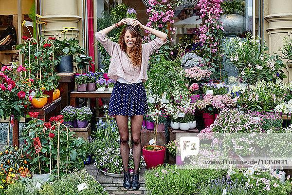 Verspielte junge Frau an einem Blumengeschäft